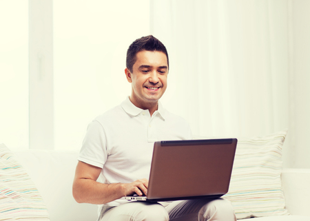 mid distance: technology, people lifestyle and networking concept - happy man working with laptop computer at home Stock Photo