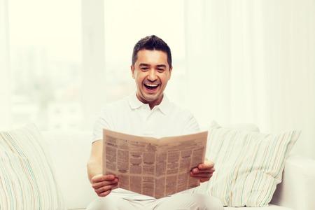 personas leyendo: ocio, información, personas y medios de comunicación concepto - hombre feliz leyendo el periódico y riendo en casa Foto de archivo