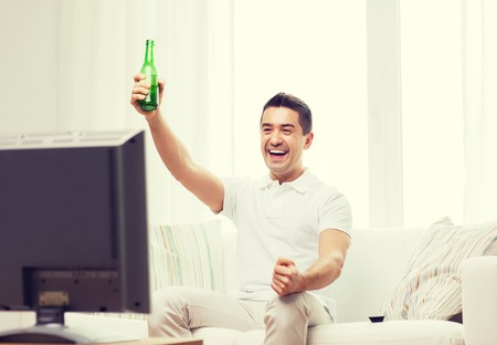 non alcoholic beer: home, people, technology and entertainment concept - smiling man with remote control watching tv and drinking beer at home