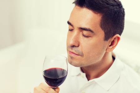 degustating: profession, drinks, leisure and people concept - happy man drinking and smelling red wine from glass at home