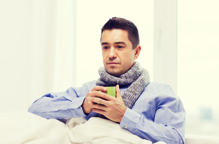 healthcare, people and medicine concept - ill man with flu drinking hot tea from cup at home