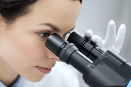 an eyepiece: science, chemistry, technology, biology and people concept - close up of young female scientist face looking to microscope eyepiece and making or research in clinical laboratory