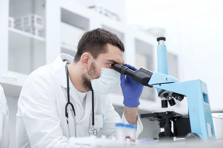 Wissenschaft, Medizin, Technik, Biologie und Personen-Konzept - junge männliche Wissenschaftler mit Reagenzgläsern uns auf Mikroskop und macht oder Forschung auf klinische Labor