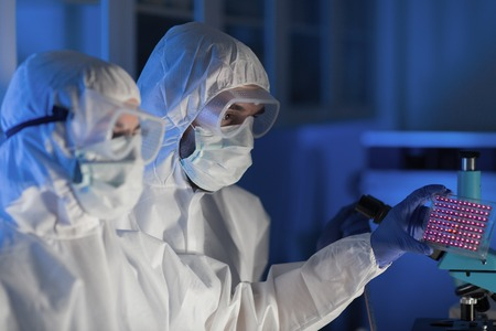 science, chemistry, medicine, research and people concept - close up of scientists looking at test sample plate in chemical laboratory