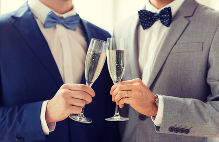 same sex: people, celebration, homosexuality, same-sex marriage and love concept - close up of happy married male gay couple in suits and bow-ties drinking sparkling wine and clinking glasses on wedding