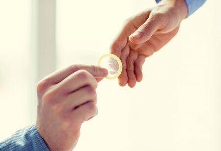 educacion sexual: personas, homosexualidad, sexo seguro, la educación sexual y el concepto de la caridad - Primer plano de felices hombres gays par de manos que dan condón Foto de archivo