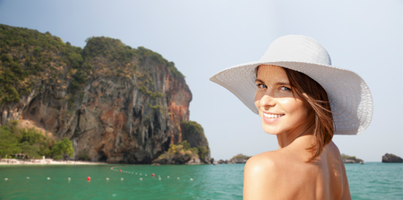 sea cliff: summer holidays, travel, people, tourism and vacation concept - happy young woman in sunhat over bali beach with cliff and sea background