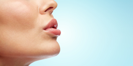 closeup view: beauty, people, make-up and plastic surgery concept - close up of young woman lips over blue background Stock Photo