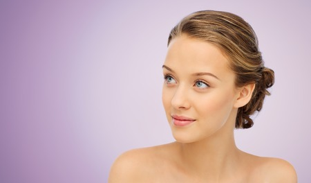 beauty woman: beauty, people and health concept - smiling young woman face and shoulders over violet background Stock Photo
