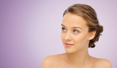 frescura: la belleza, la gente y el concepto de salud - joven cara y los hombros sonriente sobre fondo violeta Foto de archivo