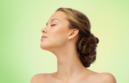 face side: beauty, people and health concept - young woman face with closed eyes and shoulders side view over green background Stock Photo