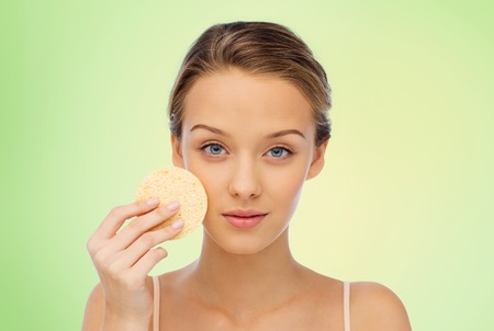 removing make up: beauty, people and skincare concept - young woman cleaning face with exfoliating sponge over green background Stock Photo