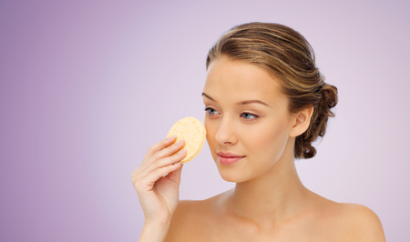 wash face: beauty, people and skincare concept - young woman cleaning face with exfoliating sponge over violet background