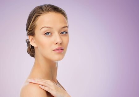 gorgeous girl: beauty, people, body care and health concept - smiling young woman face and hand on bare shoulder over violet background