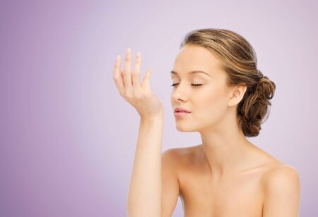 beauty, aroma, people and body care concept - young woman smelling perfume from wrist of her hand over violet background