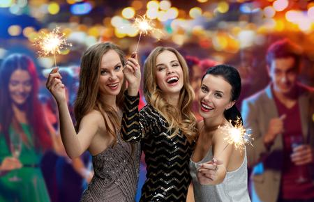 パーティ、休暇、ナイトライフ、人々 コンセプト - ナイトクラブ ライトの背景の上で花火を幸せな若い女性