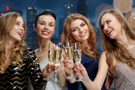 night out: celebration, friends, bachelorette party and holidays concept - happy women clinking champagne glasses over black background Stock Photo