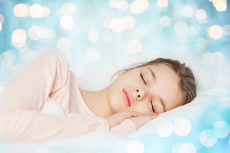 la gente, los niños, el sueño, el descanso y la comodidad concepto - niña durmiendo en la cama sobre fondo azul luces