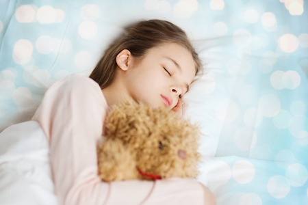 wellness sleepy: people, childhood, rest and comfort concept - girl sleeping with teddy bear toy in bed over blue lights background Stock Photo