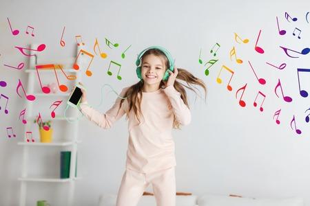 mensen, kinderen, pyjama party en technologie concept - gelukkig lachend meisje in hoofdtelefoons springen op bed met smartphone en luisteren naar muziek thuis Stockfoto