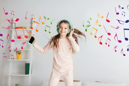 pajama: people, children, pajama party and technology concept - happy smiling girl in headphones jumping on bed with smartphone and listening to music at home