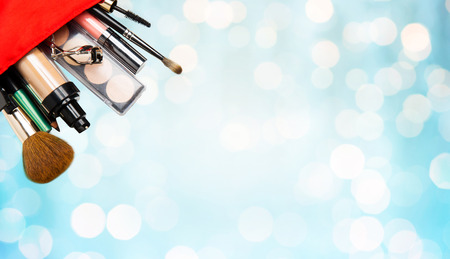 cosmetics background: cosmetics, makeup, holidays and beauty concept - close up of cosmetic bag with makeup stuff over blue lights background Stock Photo