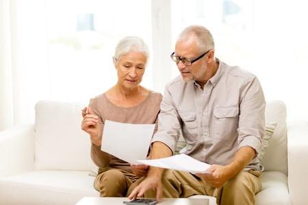 famille, affaires, économie, l'âge et les gens concept - souriant couple de personnes âgées avec des papiers et calculatrice à la maison