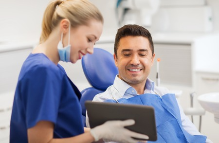 oral: people, medicine, stomatology and health care concept - happy female dentist showing tablet pc computer to male patient at dental clinic office Stock Photo