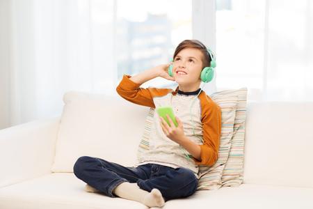 escuchando musica: el ocio, los niños, la tecnología y el concepto de la gente - niño sonriente con smartphone y los auriculares escuchando música en casa