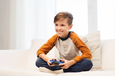pre adolescent boys: leisure, children, technology and people concept - smiling boy with joystick playing video game at home
