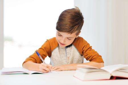 onderwijs, jeugd, mensen, huiswerk en school concept - lachende student jongen met boek schrijven naar notebook thuis