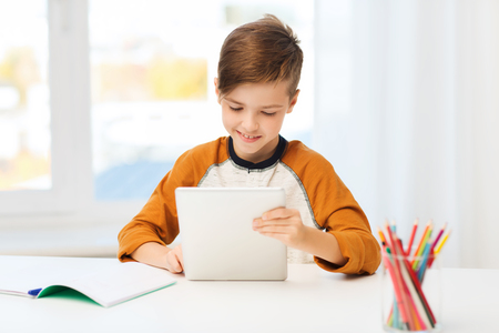computer education: leisure, children, education, technology and people concept - smiling boy with tablet pc computer and notebook at home