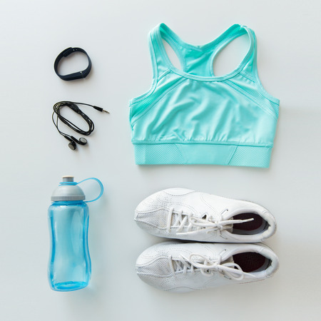 top clothing: sport, fitness, healthy lifestyle and objects concept - close up of female sports clothing, heart-rate watch, earphones and bottle set