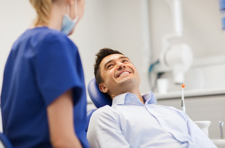people, medicine, stomatology and health care concept - female dentist talking to happy male patient at dental clinic office
