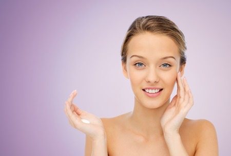 smile face: beauty, people, cosmetics, skincare and health concept - happy smiling young woman applying cream to her face over violet background Stock Photo