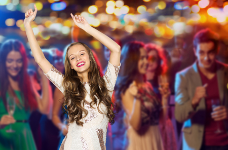 people, party, holidays, night life and entertainment concept - happy young woman or teen girl in fancy dress with sequins and long wavy hair dancing at disco club over crowd lights background