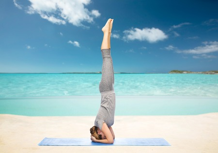 headstand: fitness, sport, people and healthy lifestyle concept - woman making yoga in headstand pose on mat over sea and sky background Stock Photo