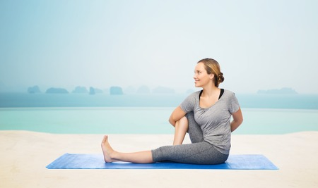 fitness, sport, people and healthy lifestyle concept - woman making yoga in twist pose on mat over infinity edge pool at hotel resort background Stok Fotoğraf