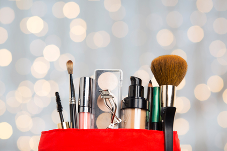 make up: cosmetics, makeup, holidays and beauty concept - close up of cosmetic bag with makeup stuff over lights background