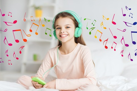 escuchando musica: la gente, los niños, el descanso y el concepto de la tecnología - la muchacha sonriente feliz despierto con el teléfono inteligente y los auriculares en la cama escuchando música en casa Foto de archivo