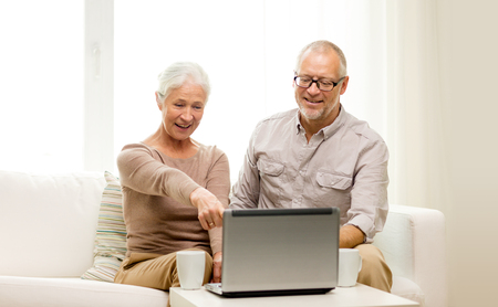 computer age: family, technology, drinks, age and people concept - happy senior couple with laptop computer and cups at home