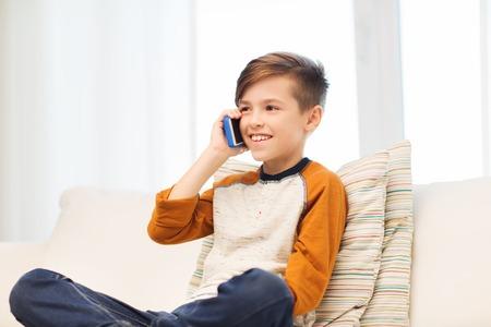 il tempo libero, i bambini, la tecnologia, la comunicazione e le persone concetto - ragazzo sorridente che invita smartphone a casa