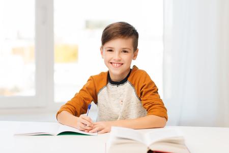 Ausbildung, Kindheit, Menschen, Hausaufgaben und Schulkonzept - Schüler Junge mit Buch schriftlich zu Notebook zu Hause lächelnd Standard-Bild