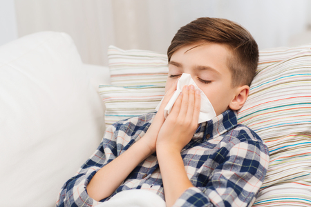 cold virus: childhood, healthcare, rhinitis, people and medicine concept - ill boy with flu lying in bed and blowing his nose at home Stock Photo