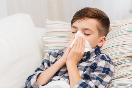 jeugd, gezondheidszorg, rhinitis, mensen en geneeskunde concept - ziek jongen met griep in bed lag en zijn neus blaast thuis