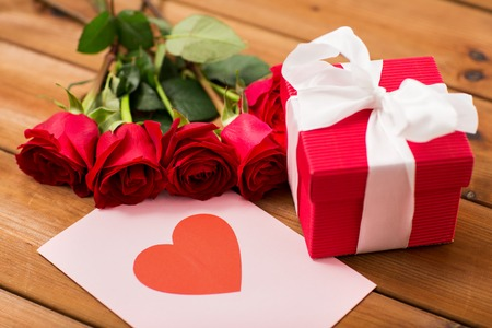 courtship: love, romance, valentines day and holidays concept - close up of gift box, red roses and greeting card with heart on wood