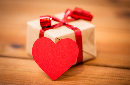 uprzejmości: love, date, romance, valentines day and holidays concept - close up of gift box and blank red heart-shaped note on wood Zdjęcie Seryjne