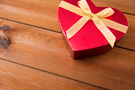 attentions: love, date, romance, valentines day and holidays concept - close up of heart shaped gift box on wood
