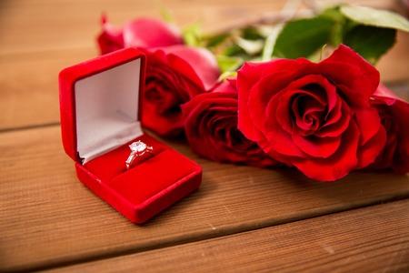 amor, oferta, el día de San Valentín y concepto de vacaciones - cerca de la caja de regalo con el anillo de compromiso de diamantes y rosas rojas en la madera