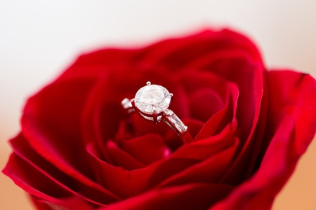attentions: jewelry, romance, proposal, valentines day and holidays concept - close up of diamond engagement ring in red rose flower Stock Photo
